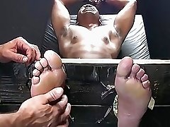 Hot chocolate stud gets his feet and cock feather tickled
