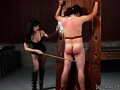 A mistress ties her slave to a pole and spanks his bare ass