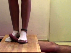 Dominant babe with sexy legs punishes a dick with her feet